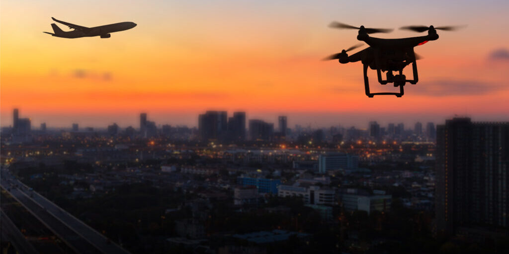 A plane and drone over sunset